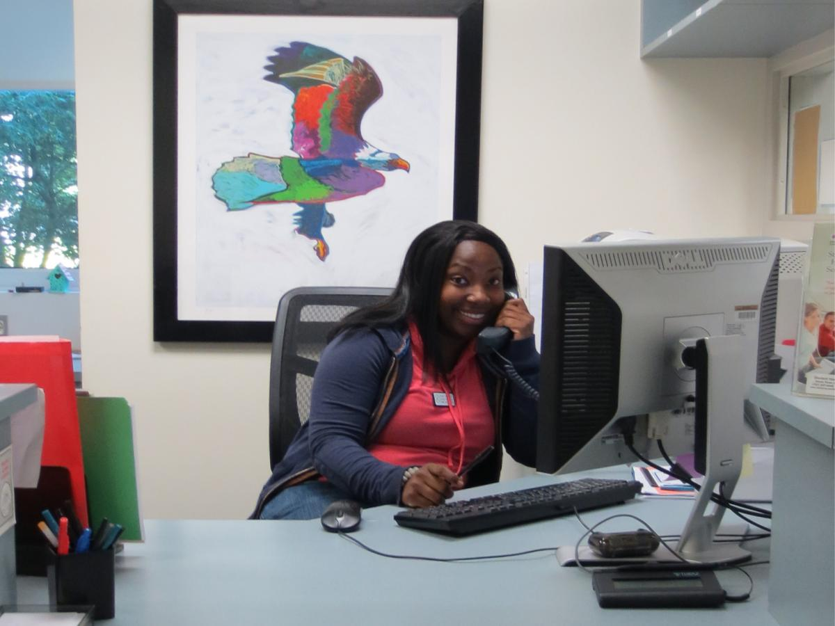 Student Health Aide answering telephone at reception desk